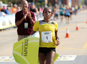 as-hirut-guangul-of-ethiopia-crossed-the-quad-cities-marathon-finish-line-as-the-first-woman-overall-for-the-fourth-consecutive-year-she-crossed-her-arms-above-her-head-in-an-x-p2