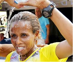 as-hirut-guangul-of-ethiopia-crossed-the-quad-cities-marathon-finish-line-as-the-first-woman-overall-for-the-fourth-consecutive-year-she-crossed-her-arms-above-her-head-in-an-x