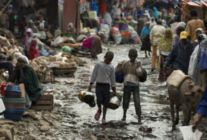 Shoppers and vendors make their way down a flooded street in Merkato, one of Africa's largest market areas, in Addis Ababa, Ethiopia Wednesday, Aug. 29, 2012. (AP Photo/Rebecca Blackwell)